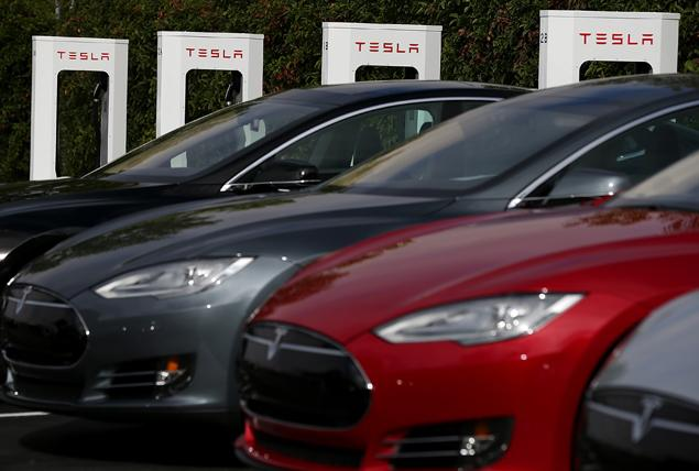 FREMONT, CA - AUGUST 16: Tesla Model S sedans are seen parked in front of a row of new Tesla Superchargers outside of the Tesla Factory on August 16, 2013 in Fremont, California. Tesla Motors opened a new Supercharger station with four stalls for public use at their factory in Fremont, California. The Superchargers allow owners of the Tesla Model S to charge their vehicles in 20 to 30 minutes for free. There are now 18 charging stations in the U.S. with plans to open more in the near future. (Photo by Justin Sullivan/Getty Images)
