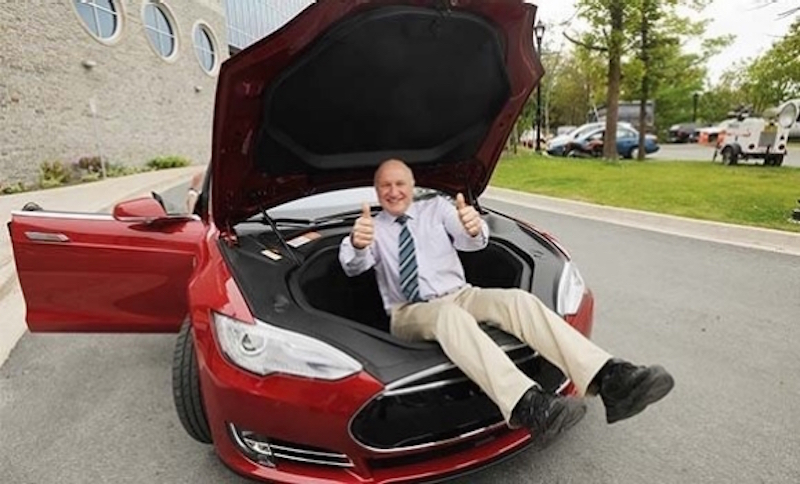 Battery expert Jeff Dahn inside the frunk of a red Model S