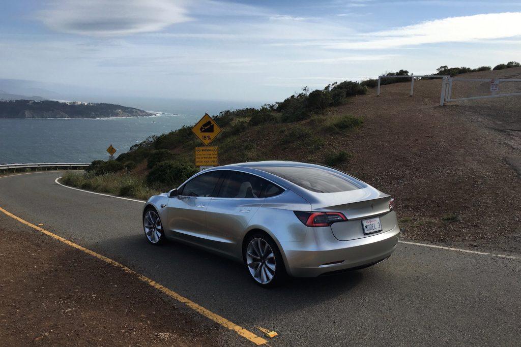 Silver Tesla Model 3 overlooking SF bay