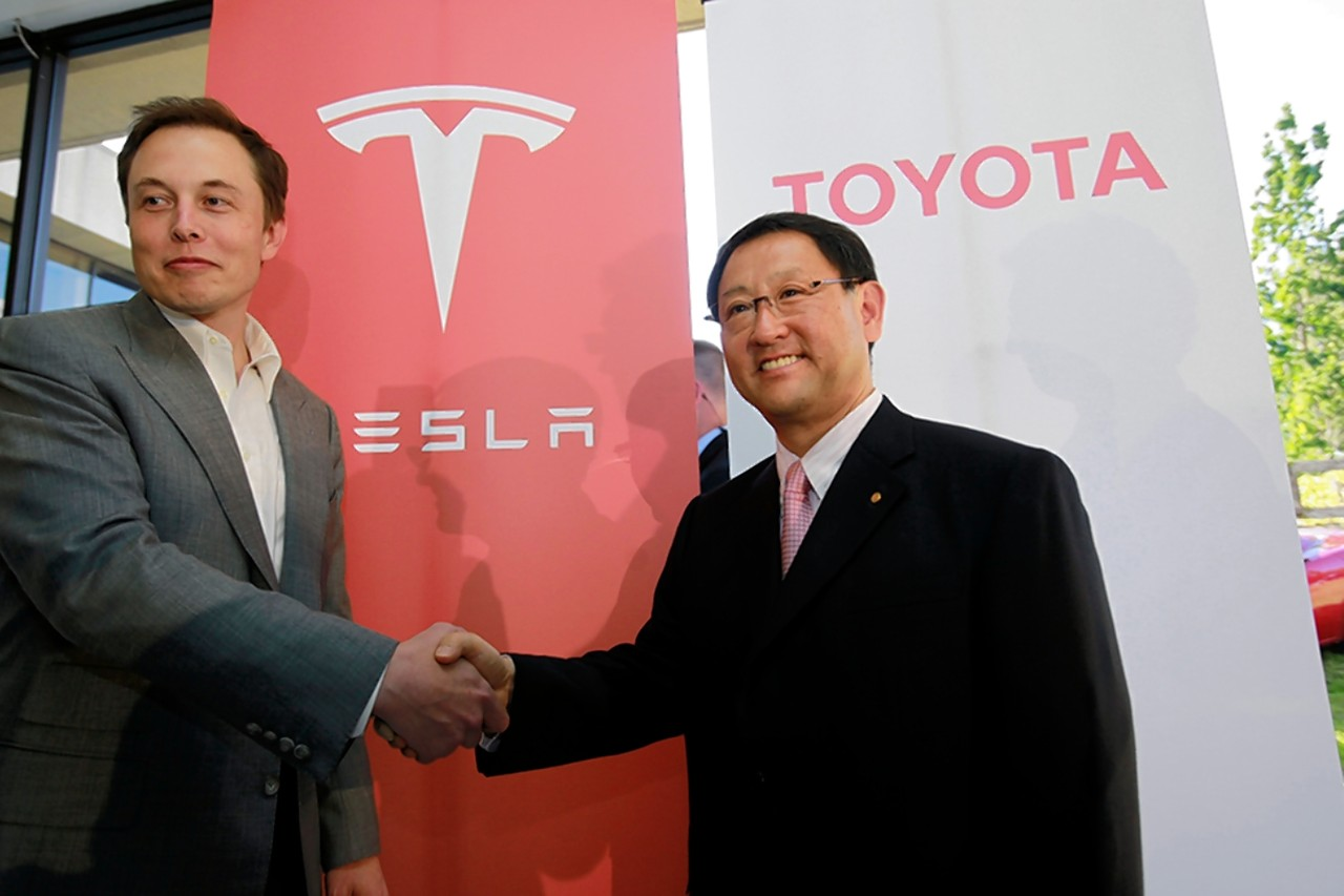 Tesla's Elon Musk and Toyota's Akio Toyoda shaking hands in Palo Alto, CA cir. 2010. [Credit: Associated Press]