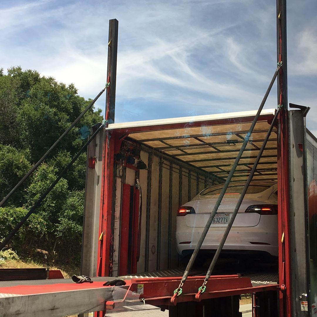 white-tesla-model-3-rear-truck-unloading