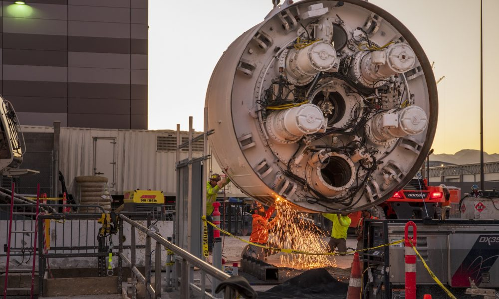 Workers cut the storage rack from the base of the drill head as the Boring Company prepares to lower the drill head for the People Mover tunnel which will connect convention halls as part of the LVCCD Phase 2 construction in the Red Lot east of the south Hall at the Las Vegas Convention center on Monday, Oct. 28, 2019. (Mark Damon/Las Vegas News Bureau)